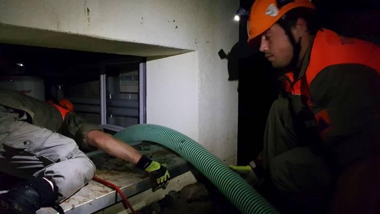 Zwei «Tiger» bringen von aussen durch ein Fenster den Ansaugschlauch der Was-serpumpe in einem mit Wasser und Schlamm gefüllten Keller in Stellung.