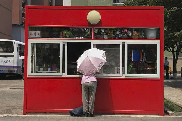 Eine Frau steht an einem Kiosk in Pjöngjang, der Blumen und Geschenke verkauft.