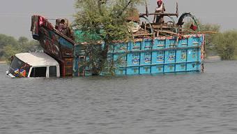 Pakistaner auf Lastwagen in den Fluten gefangen