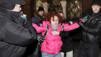 Polizisten in Zivil nehmen ergreifen eine Demonstrantin in Minsk