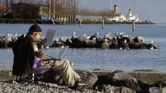 Der Bundesrat sieht Genf als idealen Standort für die Internet-Organisation. Bild: Ein Mann sitzt mit einem Laptop am Ufer des Genfersees (Symbolbild)
