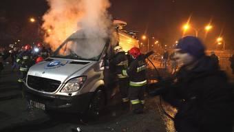 Polnische Feuerwehrleute löschen ein brennendes Auto einer Fernsehstation