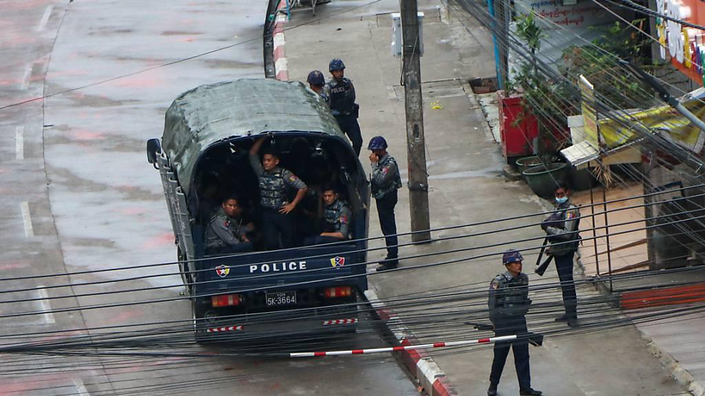 Sicherheitskräfte der Polizei warten in einem Polizeifahrzeug in Yangon. Foto: -/AP/dpa
