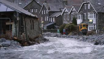 Ein über die Ufer getretener Fluss strömt durch das englische Dorf Glenridding.