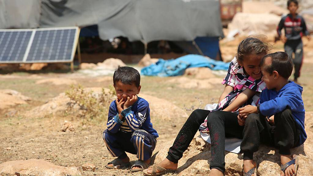 Geflüchtete Kinder sitzen in einem Flüchtlingslager nordwestlich von Aleppo auf einem Stein. (Archiv)