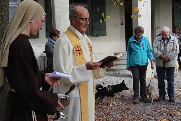 Pfarrer Beda Baumgartner bei der Segnung. Herrchen und Frauchen lauschen andächtig, ihre Vierbeiner weniger.