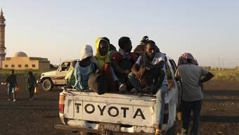 Äthiopische Flüchtlinge sitzen auf der Ladefläche eines Pick-ups. Nach Angaben des UN-Flüchtlingshilfswerks hat der wachsende Konflikt in Äthiopien dazu geführt, dass Tausende aus der Region Tigray in den Sudan geflohen sind. Äthiopiens Militär erhält in seinem Kampf gegen die Volksbefreiungsfront von Tigray (TPLF) nach deren Angaben auch Unterstützung aus Eritrea sowie einem nicht näher bezeichneten Staat außerhalb Afrikas. Foto: Marwan Ali/AP/dpa