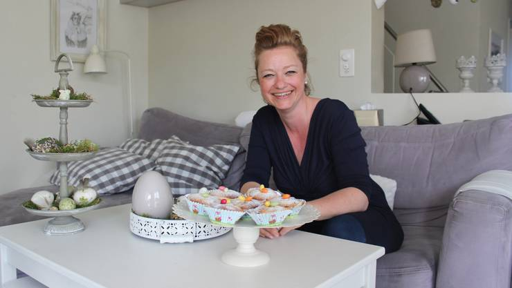 Ann Häusler präsentiert ihre Osterküchlein – die Wand hinter ihr streicht sie je nach Dekoration neu.