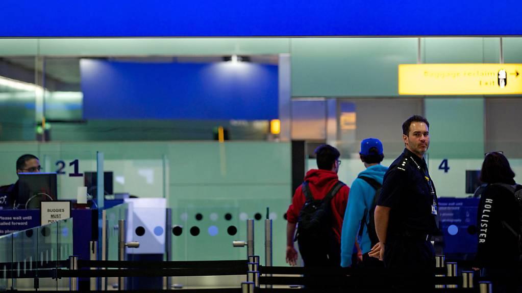 ARCHIV - Grenzbeamte stehen am Flughafen Heathrow unter einem Schild mit der Aufschrift «UK Border» (Grenze des Vereinigten Königreiches). Foto: Andrew Cowie/EPA/dpa