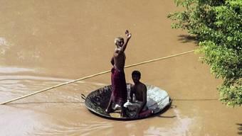 Pakistaner flüchten in einem improvisierten Boot vor den Fluten