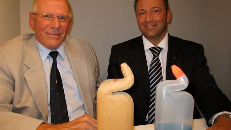 Walter Düring, der Erfinder der WC-Ente, mit seinem Sohn Heinz Düring (r.) mit einem Holzmodell und der Plastikflasche.zvg