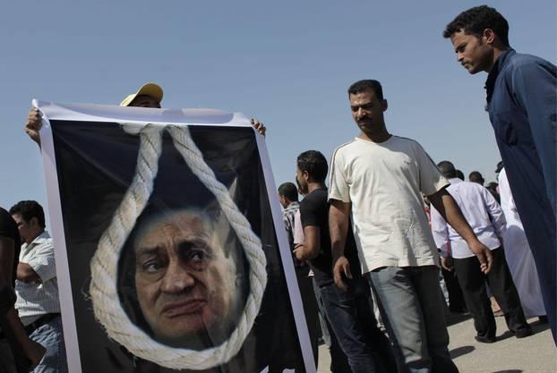 Ein Mubarak-Gegner trägt ein Plakat, das Mubarak am Galgen zeigt