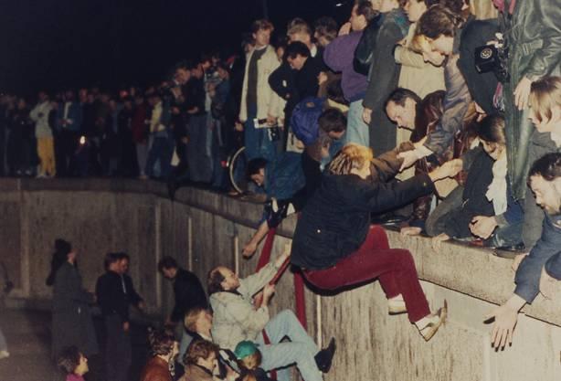 In der Nacht vom 10. November klettern Ostberliner über die Mauer.