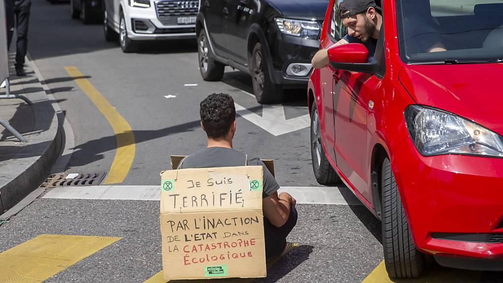 «Ich bin entsetzt über die Untätigkeit des Staates in der ökologischen Katastrophe», stand auf dem Plakat eines Aktivisten, der sich am Samstag in Genf auf die Strasse setzte.