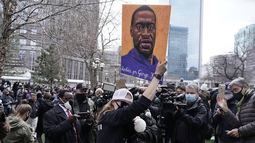 Menschen jubeln und halten ein Poster von George Floyd hoch nach der Urteilsverkündung im Mordprozess gegen den ehemaligen Polizeibeamte Derek Chauvin. Foto: Morry Gash/AP/dpa
