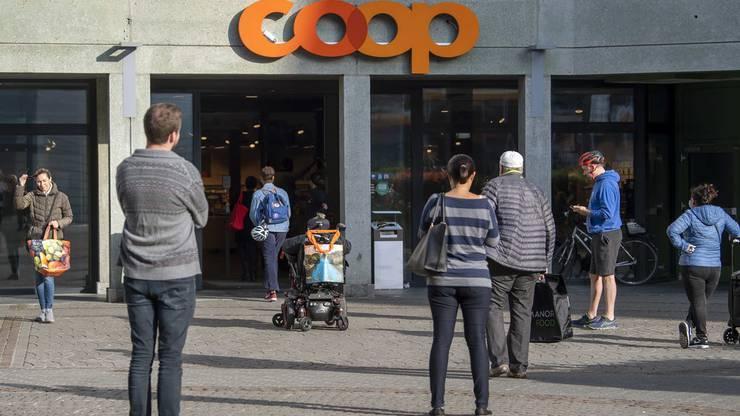 Die Menschen stehen Schlange vor einer Coop-Filiale.