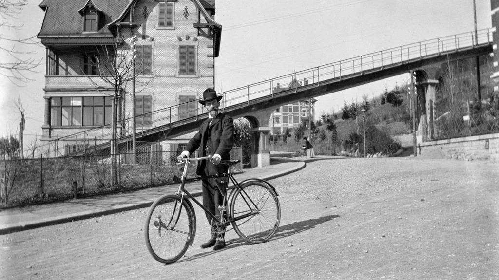 Ein Mann mit Fahrrad vor einer Bruecke der Seilbahn Rigiblick in Zuerich, aufgenommen um 1901