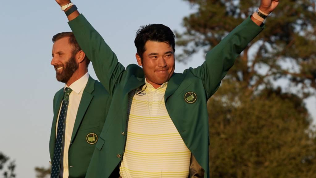 Hideki Matsuyama jubelt im Grünen Jackett des US-Masters-Siegers. Links Vorjahressieger Dustin Johnson