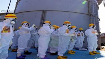 Im September liess sich der japanische Premierminister Shinzo Abe (mit rotem Helm) in Fukushima vor Ort erklären, dass die Tanks für radioaktiv verseuchtes Wasser immer noch lecken. Keystone