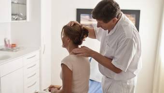 Ein Hausarzt untersucht eine Patientin (Archiv)