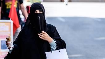 In Interlaken gibt es besonders viele Touristen aus dem arabischen Raum. Die Frauen tragen oft Burka oder Niqab, welche in Europa für Kontroverse sorgen. Eine Frau trägt eine Burka und isst darunter ein Glacé.