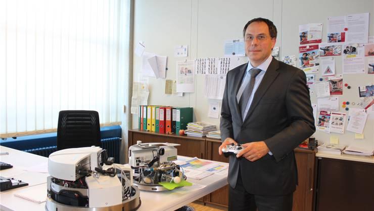 Direktor Michael Benker zeigt in seinem Büro zwei von Studenten konstruierte Roboter.
