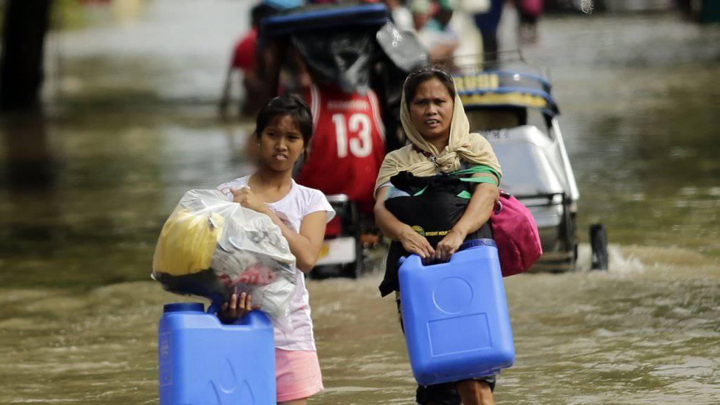 Die Bewohnerinnen von La Paz im Süden der Philippinen kommen nur mühsam auf den überfluteten Strassen voran.