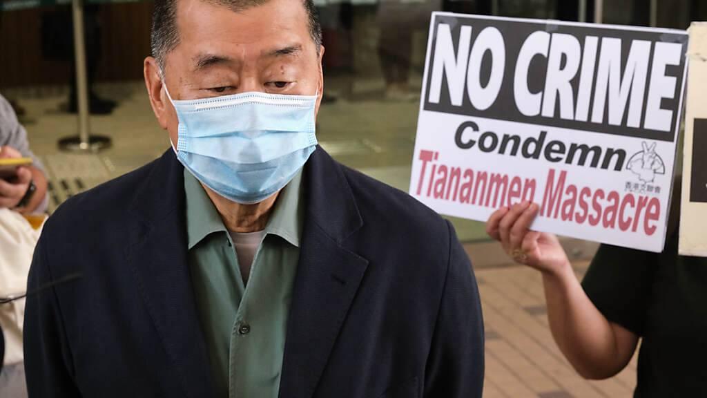 ARCHIV - Ein Unterstützer hält ein Schild mit der Aufschrift «No Crime - Condemn Tiananmen Massacre» (Kein Verbrechen - Tiananmen Massaker verurteilen) in der Hand, als der regierungskritische Medienunternehmer Jimmy Lai am Amtsgericht von West Kowloon ankommt. Foto: Isaac Wong/SOPA Images via ZUMA Wire/dpa