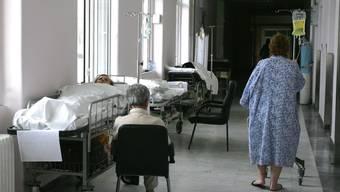 Ein Patient im Erythros Stavros Spital in Athen wartet im Korridor auf ein Zimmer. Wegen Personalmangel in griechischen Spitälern und Lohnkürzungen streiken die Spitalangestellten. (Archivbild)