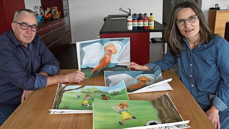 Martin Willi und Regina Erhard mit den Originalbildern für ihr erstes Kinderbuch.
