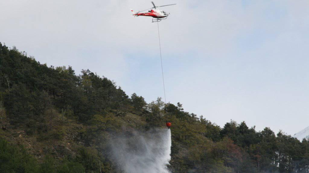 Ein Helikopter bekämpft am Mittwoch das Feuer in einem Waldstück bei Lens VS. (Archiv)