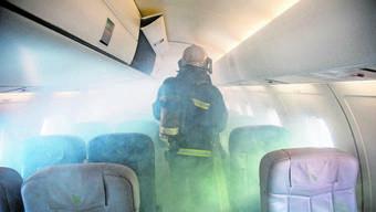 Einsatz in der Kabine: Ein Feuerwehrmann am Flughafen Bern-Belp prüft den Ernstfall. Der Euro-Airport hat für solche Zwecke eine Fokker 27 – noch.