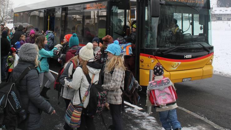 Schülerinnen und Schüler besteigen bei der Haltestelle Schulhaus Lüterkofen das Postauto.