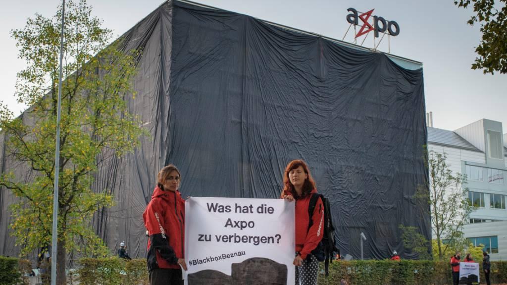 Greenpeace-Aktivisten hüllen das Axpo Hauptquartier in Baden mit einem schwarzem Tuch ein.