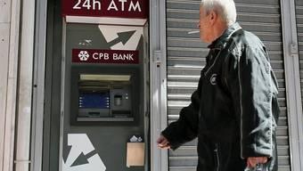 Ein Mann geht an einem Bancomaten vorbei (Archiv)