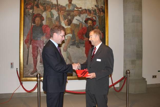 Gerber dankt dem Berner Kirchendirektor Christoph Neuhaus (links) für sein Engagement mit einem kleinen Geschenk