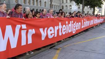 """Gewerkschafter vor dem Bundeshaus demonstrieren mit einer """"Roten Linie"""" für die flankierenden Massnahmen."""