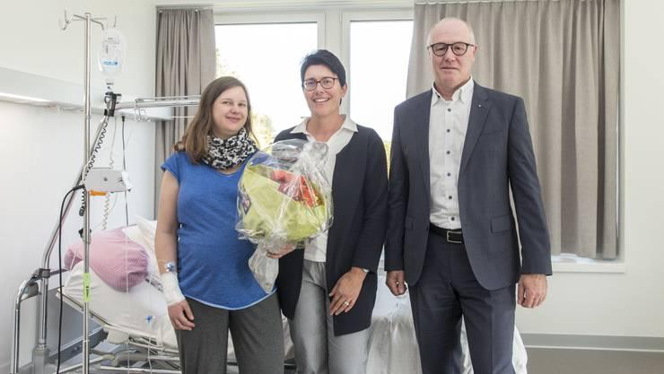 Einen Strauss Blumen für die erste Patientin. Pflegedirektorin Susanne Vanini (Mitte) und Spitaldirektor Thomas Brack statten Silvia Marton einen Besuch ab.