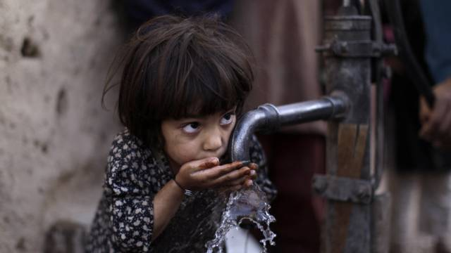 Flüchtlingsmädchen trinkt von Wasserpumpe in Slum von Islamabad