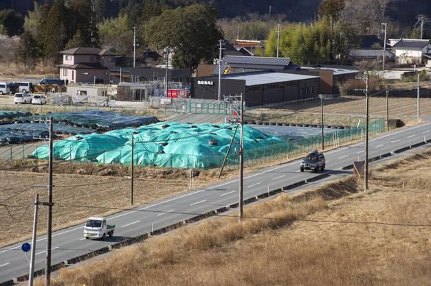 Neben der Strasse liegen Säcke voller radioaktiv kontaminierter Erde.