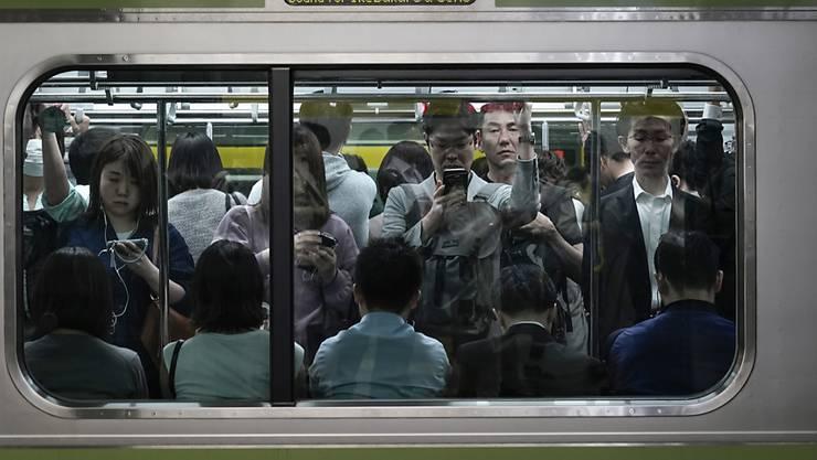 Ein mit Fahrgästen vollgepackter Eisenbahnwagen in Tokio. (Archivbild)
