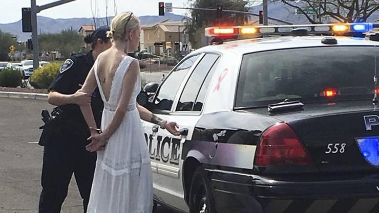 Die Braut wird in Handschellen zu einem Polizeiauto gebracht.