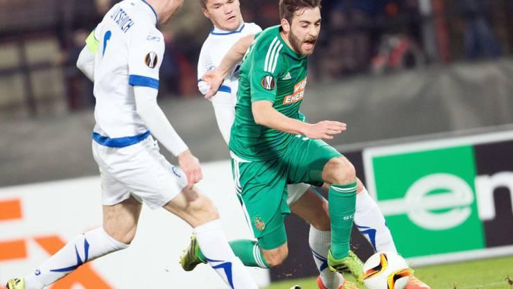 Rapid Wiens Thanos Petsos (grün) kann sich gegen zwei Dynamo-Verteidiger durchsetzen