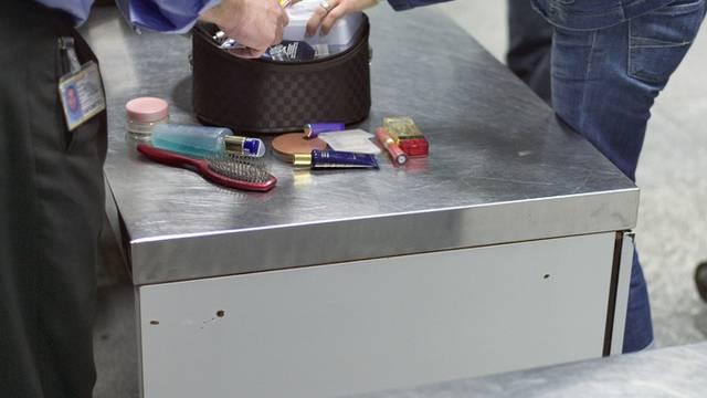 Ein Zollbeamter am Flughafen Zürich kontrolliert das Gepäck einer Frau (Archiv)