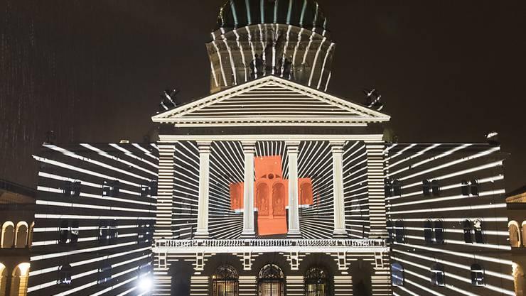 """Das Lichtspektakel """"Rendez-vous Bundesplatz"""" projiziert neue Bilder an die Fassade des Bundeshauses. Die neue Lichtshow ist dem 150. Geburtstag des Schweizerischen Roten Kreuzes (SRK) gewidmet."""