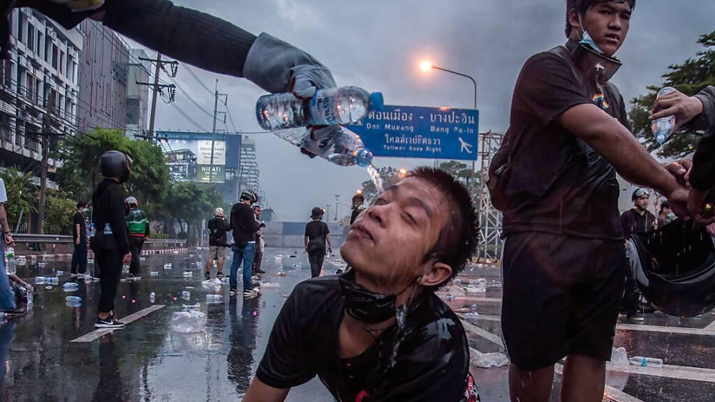 Ein Demonstrant spült die Augen eines weiteren Demonstranten aus bei einem Protest gegen die Corona-Politik. Trotz Verbots öffentlicher Versammlungen protestierten Hunderte Demonstranten am Siegesdenkmal gegen die Regierung und fordern den Rücktritt des Premierministers.