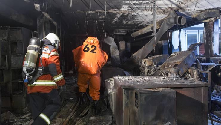 Feuerwehrleute kämpfen sich, kurz nachdem das Feuer gelöscht wurde, durch das Fabrikgebäude. (Archiv)