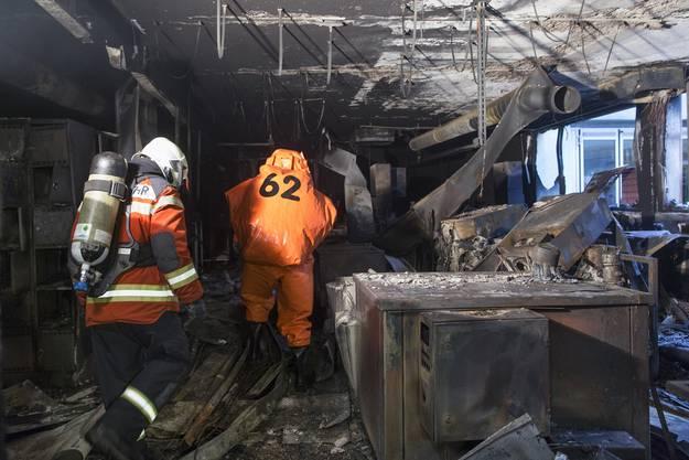 Feuerwehrleute kämpfen sich durch das Fabrikgebäude.