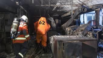 Feuerwehrleute kämpfen sich durch das Fabrikgebäude der Eta. (Archiv)