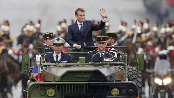 ARCHIV - Der französische Präsident Emmanuel Macron (M) wird in einem Militärfahrzeug bei einer Parade über die Champs-Elysees in Paris gefahren. Frankreich verzichtet wegen der Corona-Krise auf die traditionelle Militärparade am Nationalfeiertag 14. Juli. Foto: Michel Euler/Pool AP/dpa